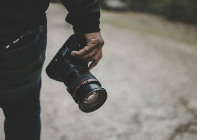 a hand of a man holding a camera