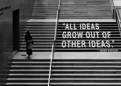 """A woman walking down a flight of stairs with a caption that reads, """"All ideas grow out of other ideas."""" -Anish Kapoor"""