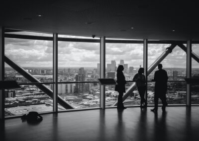 a black and white photo of 3 people overlooking a city skyline