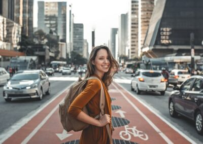 a woman smiling at the camera standing in a bike line between traffic