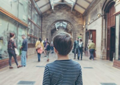 the back of a boy in the middle of a large corridor with people in the background