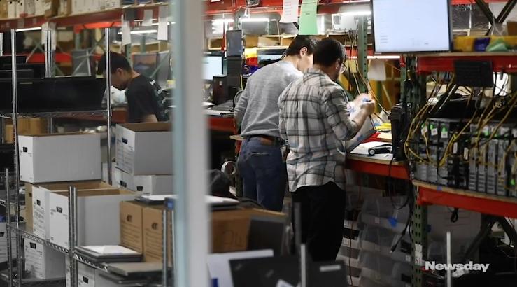 Several Employees work at refurbishing computer equipment.