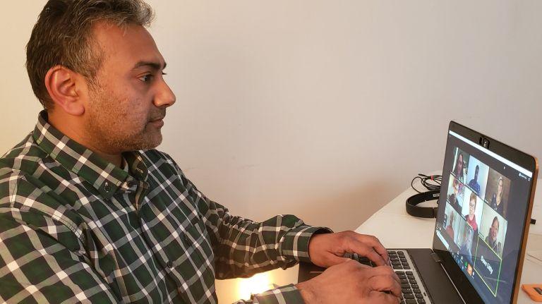 Vikram Rajan, co-founder of Kings Park-based phoneBlogger.net & Videosocials.net, works on a remote client call. Credit: Practice Marketing, Inc.